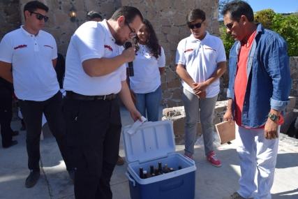 El Dr. Lino Briones, del Comité de Recepción de vinos entregando al Jurado Calificador los vinos a catar